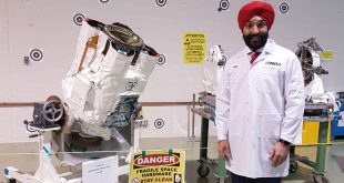 The Honourable Navdeep Bains stands in front of the Canadarm2 Latching End Effector spare that will launch to the ISS in 2018.