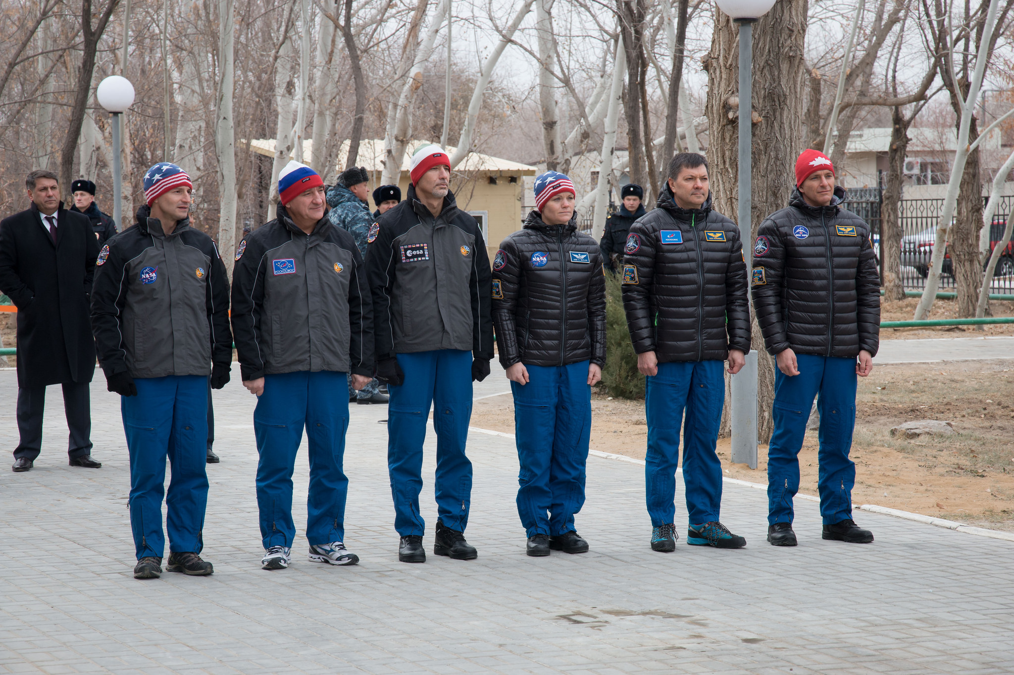 Outside the Cosmonaut Hotel crew quarters in Baikonur, Kazakhstan, the Expedition 58 prime and backup crew members attend a flag-raising ceremony Nov. 21, part of their traditional pre-launch activities. From left to right are backup crewmembers Drew Morgan of NASA, Alexander Skvortsov of Roscosmos and Luca Parmitano of the European Space Agency and prime crewmembers Anne McClain of NASA, Oleg Kononenko of Roscosmos and David Saint-Jacques of the Canadian Space Agency. McClain, Kononenko and Saint-Jacques will launch Dec. 3 on the Soyuz MS-11 spacecraft from the Baikonur Cosmodrome in Kazakhstan for a six-and-a-half month mission on the International Space Station