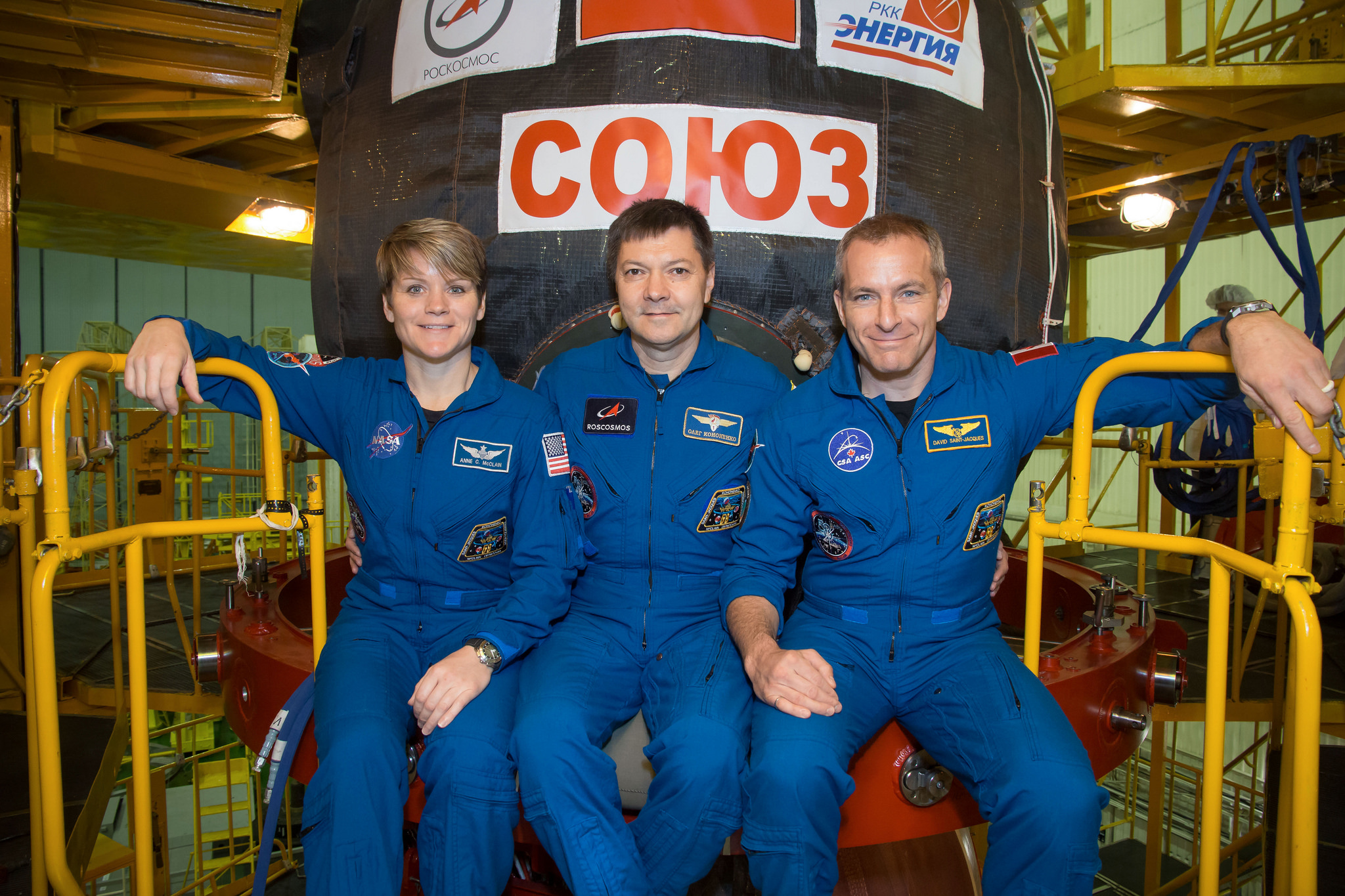 In the Integration Facility at the Baikonur Cosmodrome in Kazakhstan, Expedition 58 crew members Anne McClain of NASA (left), Oleg Kononenko of Roscosmos (center) and David Saint-Jacques of the Canadian Space Agency (right) pose for pictures Nov. 20 in front of their Soyuz MS-11 spacecraft during a vehicle fit check. They will launch Dec. 3 on the Soyuz MS-11 spacecraft from the Baikonur Cosmodrome for a six-and-a-half month mission on the International Space Station