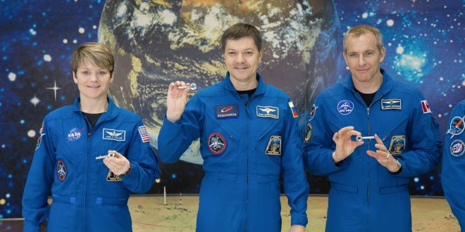 "At the Baikonur Cosmodrome Museum in Kazakhstan, Expedition 58 crew members Anne McClain of NASA (left), Oleg Kononenko of Roscosmos (center) and David Saint-Jacques of the Canadian Space Agency hold ""launch keys"" presented to them Nov. 29 during a tour of the facility. An actual key is used on launch day to begin the engine ignition sequence for the Soyuz booster rocket's liftoff. They will launch Dec. 3 in the Soyuz MS-11 spacecraft from the Baikonur Cosmodrome in Kazakhstan for a six-and-a-half month mission on the International Space Station"