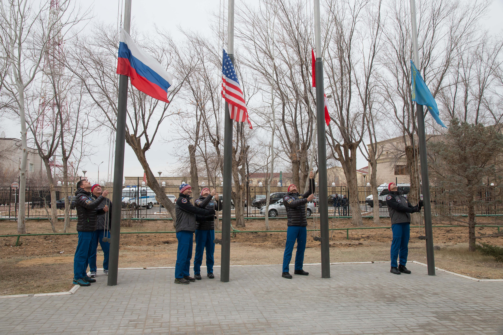 Outside the Cosmonaut Hotel crew quarters in Baikonur, Kazakhstan, the Expedition 58 prime and backup crew members raise the flags of Russia, the United States, Canada and Kazakhstan Nov. 21 in a traditional ceremony. Anne McClain of NASA, Oleg Kononenko of Roscosmos and David Saint-Jacques of the Canadian Space Agency will launch Dec. 3 on the Soyuz MS-11 spacecraft from the Baikonur Cosmodrome in Kazakhstan for a six-and-a-half month mission on the International Space Station