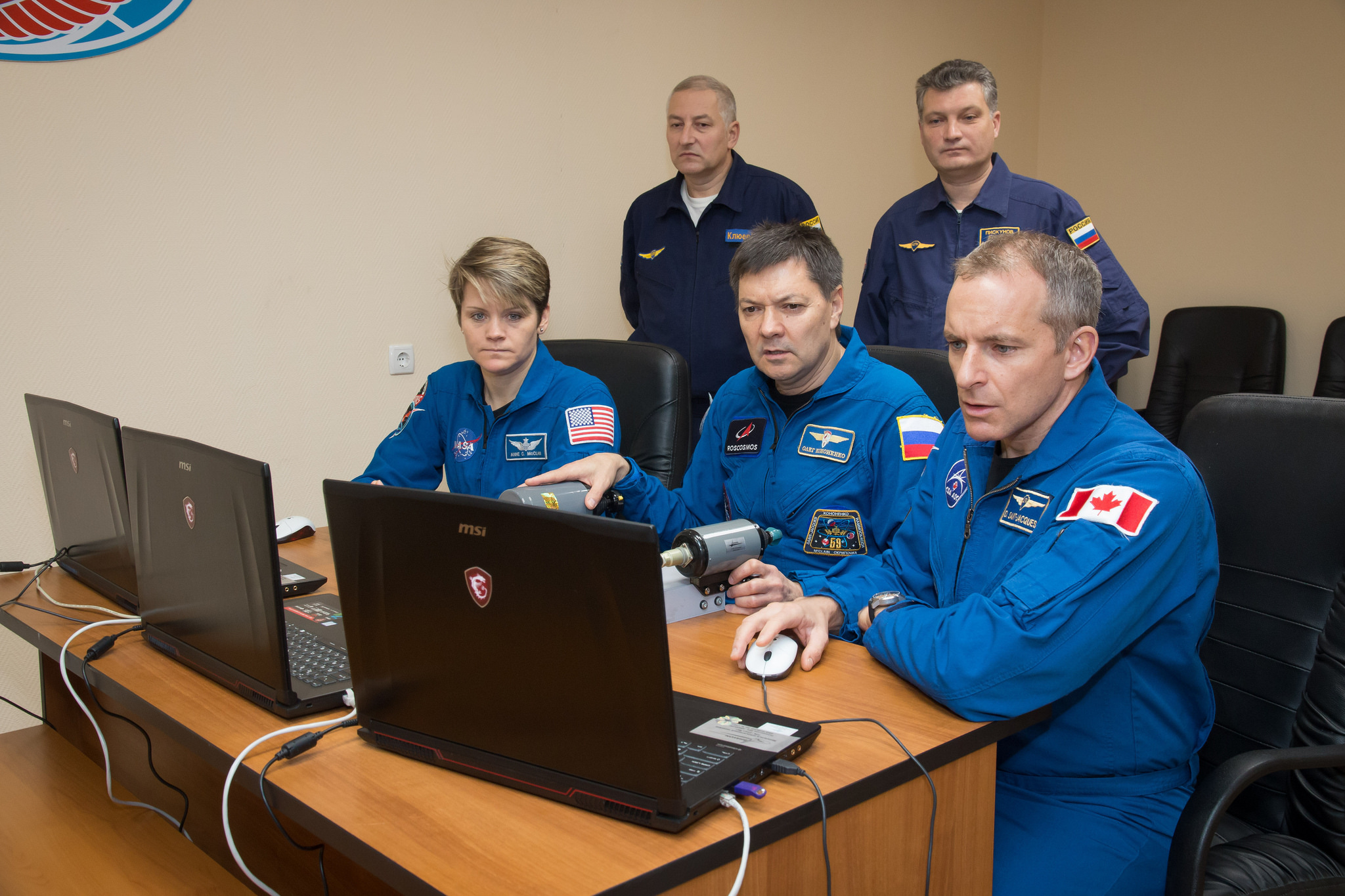 Anne McClain of NASA (left), Oleg Kononenko of Roscosmos (center) and David Saint-Jacques of the Canadian Space Agency (right) practice rendezvous techniques on a laptop computer Nov. 27 as part of their pre-launch training.